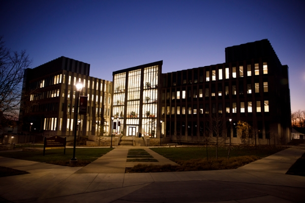 Luddy Hall, lit from the inside against a the backdrop of the night sky