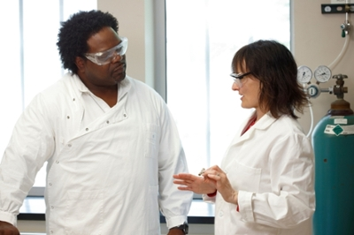 Researchers Dean Rowe-Magnus and Nicola Pohl in lab coats discussing their work