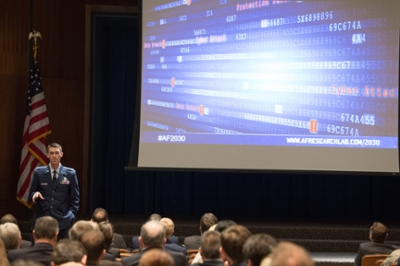 Man in uniform stands before projection screen at conference