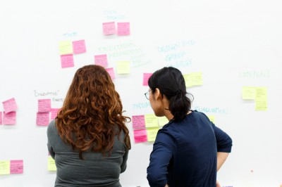 A student and faculty member look at notes on a whiteboard.