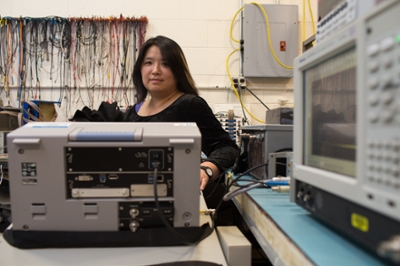 A female researcher stands in a physics lab among machines and wires