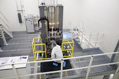 A researcher in smock and protective head/footwear crouches by a piece of machinery