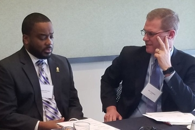 Two men in business suits and wearing conference ID tags discuss while sitting at a table