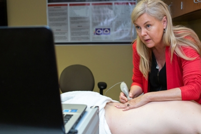 A clinical massage therapist uses a device on a patient's back