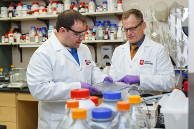 Two researchers in goggles and white coats stand talking in the lab amongst many-colored bottles