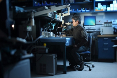 A researcher sits in a lab, looking through a microscope.