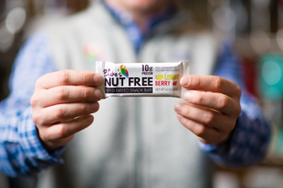 A person holds the nut-free snack bar in both hands