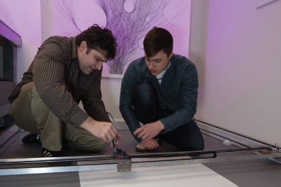 A student and a professor work on the floor with the drawing robot