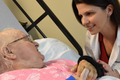 Dr. Kathleen Unroe talks to a patient at her bedside