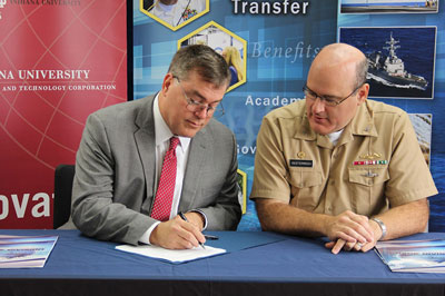 IU VP for Research Fred Cate signs agreement with Capt. Mark Oesterrech of Crane