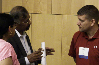 Two businesspeople talk with an Indy Chamber rep at connection event