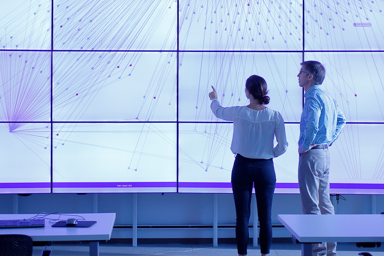 Two people look at a Hoaxy visualization on a big screen