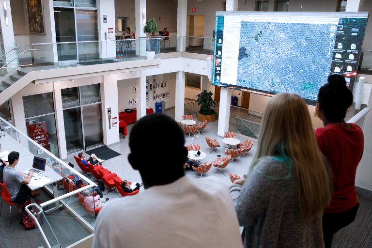 Students watch news on a large screen in The Media School at Indiana University.